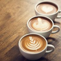 cups of coffee with designs in foam