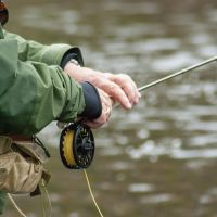 Fly-fisherman holding rod and reel